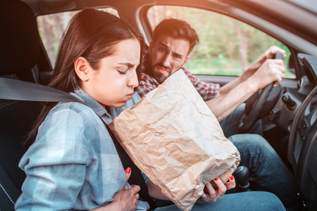 A picture of sick girl holding a bag and trying to vomit into it. She feels bad. Girl is holding her hand on stomach. Guy is looking at her with sight full of disgution. Stockfoto