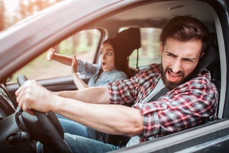 Bearded man is driving car. They are riding too fast. Guy is keeping his eyes closed but still driving car. Girl is keeping her hands in front of her. She is trying to defence herself.