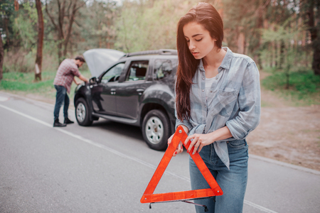 Nice and serious girl is standing on the road and holding the sign pf red triangle. She is looking down. Guy is standing besides car and fixing it.