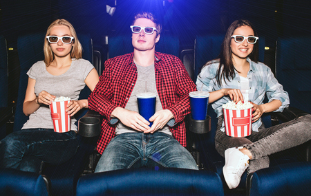 Young people are sitting in chairs in cinema. They wear glasses for watching movies. Guy has cup of coke while girls have basket of popcorn. They are watching movie. Blonde girl is looking on camera. 写真素材