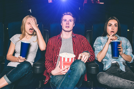 Youn man and women are sitting in chairs and watching movie. They are surprised and confused. Blonde girl put her hand on face. Brunette girl stopped drinking cola. Guy is holding a basket of popcorn.