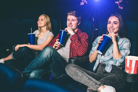 Nice people are sitting together in a cinema room. They are drinking coke and having fun. All of them are smiling and all of them has pun one leg on another.