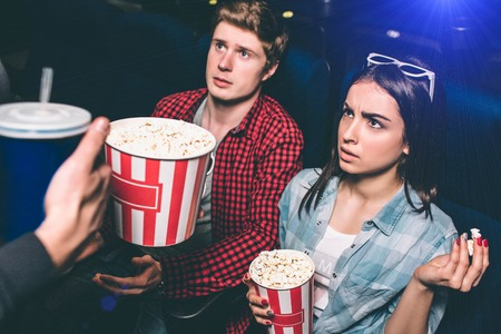A picture of unhappy and not satisfied young couple. They are looking to man that distract them from watching movie. Girl is angy and guy is amazed. Foto de archivo - 101330414