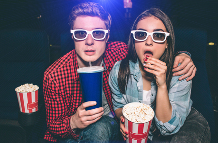 Portrait of two people sitting together in cinema hall and wearing glasses. Girl is amazed and eating popcorn while her partner is drinking cola.