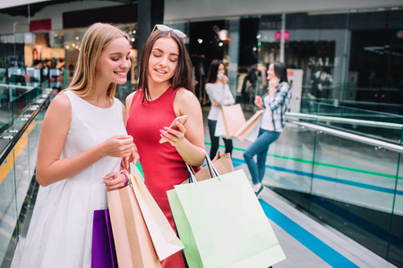Attractive and beautiful girls are standing together with bags. Brunette girl is holding phone and looking at it together with her friend. Blonde girl is smiling. Their friends are standing behind. Stock Photo