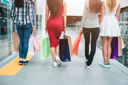 A picture of girls back. They are walking. Young women have colorful bags in hands. They are shopping together.