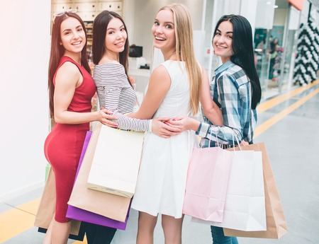 Happy and positive women are standing together and posing. They are looking back on camera and smiling. Also they have many bags in their hands. Girls had productive shopping.