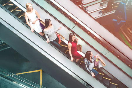 Young ladies are riding on escalator. They are standing one after another. Each of them has shopping bags. They are going down.