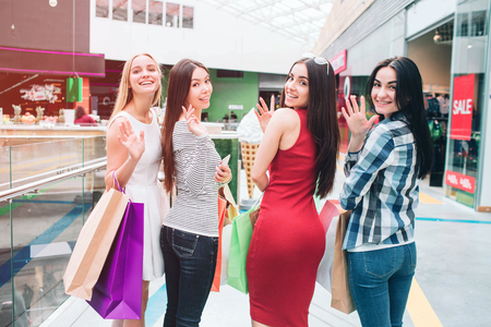Awesome and well-dressed girls are standing and posing. They are looking backwards on camera, waving and smiling. They look happy. Stock Photo