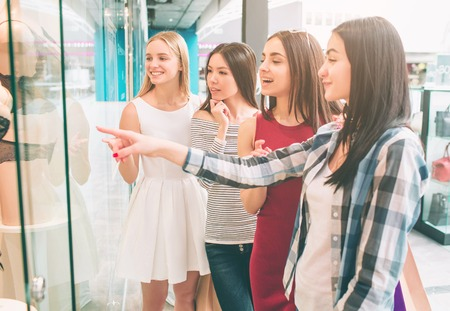 Girls are standing at the showcase of lingerie store and looking at Mannequin with interest. Brunette is pointing on Mannequin