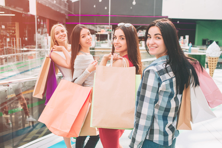 Girls are standing and posing. They are looking backwards and smiling. They are holding bags on their shoulders.