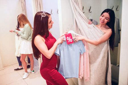 Asian girl is taking blue and pink discount shirts from girl in red dress. She wants to try them on herself. There are other two girls in dressing room standing in line.