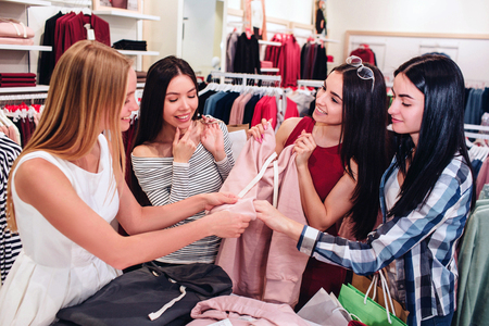 Four friends are standing together and holding one pink sweatshirt. Girls are looking at it and smiling. They are very excited. Stock Photo