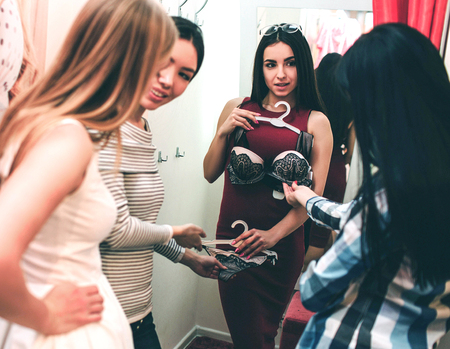 Beautiful girl in red dress is trying on herself bra. She is looking at her friends while they are looking at bra and talking about it. They are standing in a dressing room.