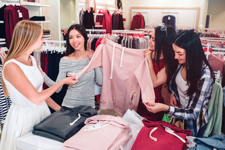 Pretty ladies are in store. They are holding one pink sport sweatshirt. Asian girl is looking at blonde one and smiling while brunette girl is looking at blouses sleeve.