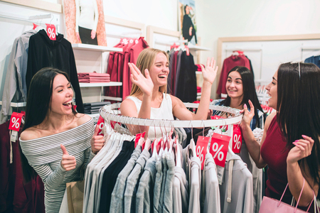 Happy and funny young women are standing together near round hanger and having some fun. They are waving with their hands and laughing.