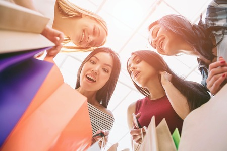 Colorful picture of girls holding colorful bags. They are looking down into one bag and wondering. Girls are looking very amazed and excited. Stock Photo