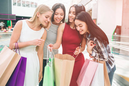 Well-dressed and attractive young women are standing together and looking into one bag. Girl in red dress is holding thet bag. She is sharing her happiness with friends. Stock Photo