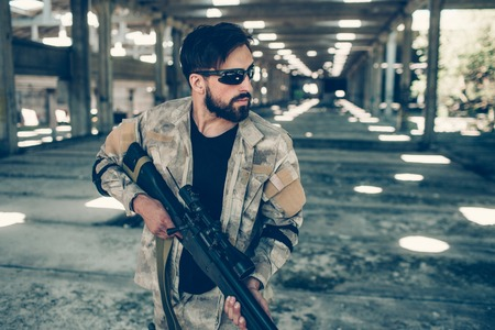 Serious and handsome man in glasses is standing in hangar and holding paintball gun in hands. He is looking straight forward. Man wears special uniform.