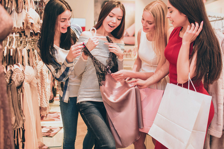 Asian girl is holding lace night shirt. It is very beautiful. Girls are looking at this shirt as well and touching it. They are amazed and excited.
