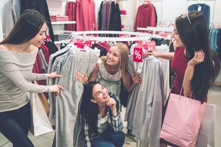 Funny picture of blonde and brunette girls are found under the round hanger and looking at their friends. They are smiling. Girls are having fun.