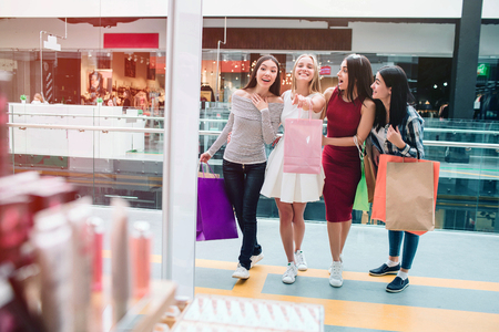Blonde girl is looking forward and pointing. She is very excited. Other girls are looking in the same direction. They are happy and excited as well. They are standing at the entrance of store.