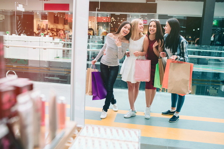 Cheerful and delightful young women are standing at entrance of store and looking inside it. They are very happy and excited. Girls are looking at each other with smile.