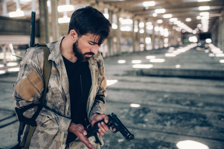 Serious professional is recharging his gun. He is holding his right hand at the low edge of pistol. Guy is looking at it. Young man is in big hangar. Stock Photo