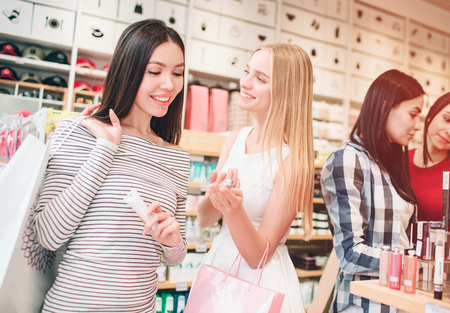 Two nice girls in the front are standing and smiling. Asian girl is looking at cosmetics that blinde girl has in her hand. Blonde girl is looking to asian girl and smiling. Stock Photo