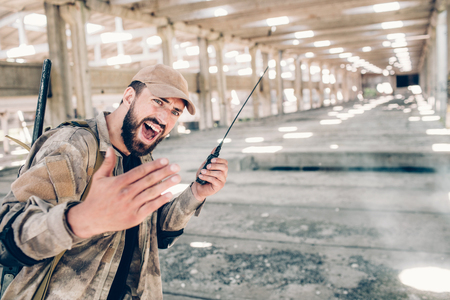A picture of lonely bearded man in hangar. He is holding portable radio in left hand and using it. Guy is screaming. Also young man is keeping his right hand fingers together.
