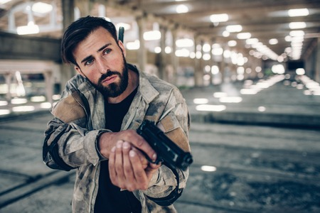 Handsome and attractive guy is standing in an empty hangar. He is alone there. Young man is holding black gun in his hands in a position ready to shoot. He is listening for his enemies.