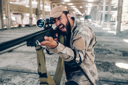 Horizontal view of military soldier screaming and yelling. He is taking aim by using big rifle. Man wears military uniform. He is ready to fight and shoot.