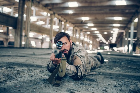 A picture of fighter lying on the floor in big hangar. He is looking straight forward through lens and taking aim on camera. Man is very serious. He is ready to start a fight.