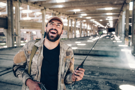 Happy and cheerful bearded fighter is looking up. He wears special sand-colored uniform. Man has portable radio in one hand and black guy in right one. He is in big hangar alone. Stock Photo