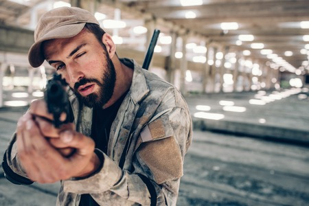 Guy is taking aim. He is looking straight forward on camera. He wears military uniform. Man is serious and concentrated. Stock Photo