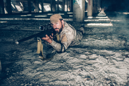 Serious and professional man is lying on the ground and looking through lens. He is taking aim. Guy wears military clothes. He is waiting.