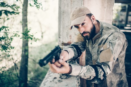 Concentrated and courageous man is standing near exit and holding gun in his hands. Man is holding finger on trigger. Hireling is calm. He is waiting. Stock Photo