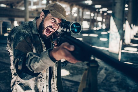 Fighter is looking through lens on rifle and taking aim. He is holding it with both hands. Emotional guy is screaming and yelling. He is in a big hangar alone. Stock Photo