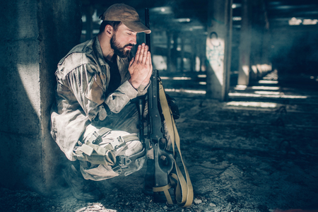 Spiritual man is sitting in squat position and praying. He is keeping his eyes closed and holding hands together close to face. Also there is a rifle near his knees.