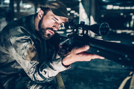 Portrait of brunette is taking aim. He is looking through lens. Guy is holding rifle with right hand and keeping his left one on trigger. Man is ready to shoot. Stock Photo