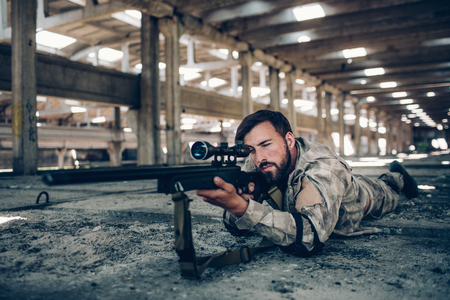 Attractive and serious guy is lying on the ground in a big hangar. He is taking aim. Man in looking through lens. He is very calm and concentrated.