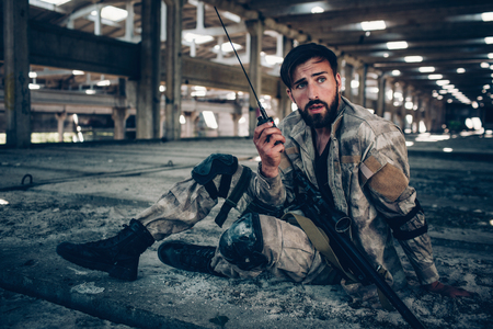 Nice picture of attractive and handsome brunette sitting on the ground. He is holding portable radio in left hand. Rifle is lying on his left leg. Guy is looking to the right. Stock Photo