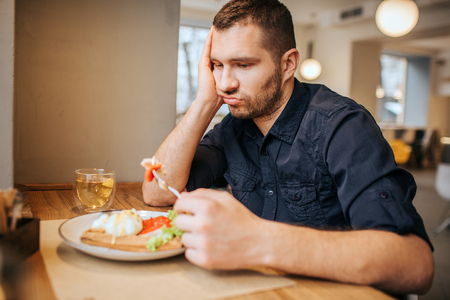 Bored and sad man is sitting at table and cafe. He is holding a piece of vegetable on fork. Man is looking at it and breathing out. Reklamní fotografie