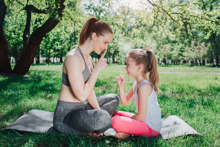 Funny picture os girls sitting on carimate outside in park and showing the hush symbol to each other. They are smiling and laughing a bit. Yoga and Pilates Concept. Stock Photo