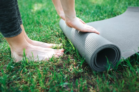 A picture of females legs and hands. Girl is rolling up the carimate. Close up. Yoga and Pilates Concept.