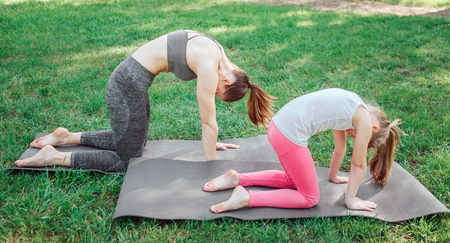 Two girls are standing on carimate and holding their back curved. They are balancing in that pose. Girl are concentrated on this excercise. 写真素材