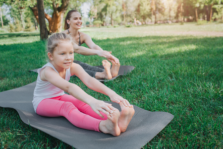 女の子は前に座って、彼女のお母さんが背中にイストと同じことをしている間、彼女の体を伸ばしています。彼らは足を一緒に保ち、まっすぐ前を向いています。