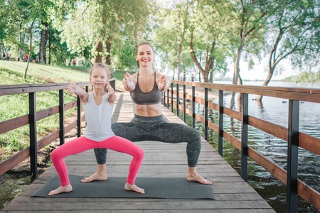 Happy and good-looking girls are standing in a squat position and pulling their hands straight forward. They are smiling. Girls are working out at small bridge. 写真素材