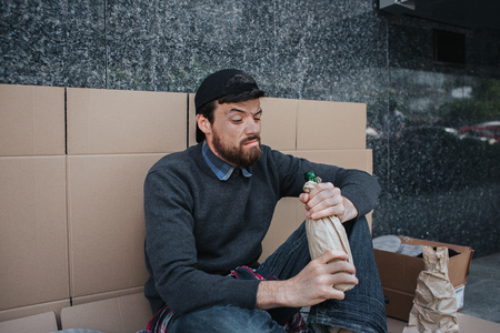 Homeless man is sitting and leaning to the wall with cardboard. He is looking inside the bottle with alcohol. Stock Photo