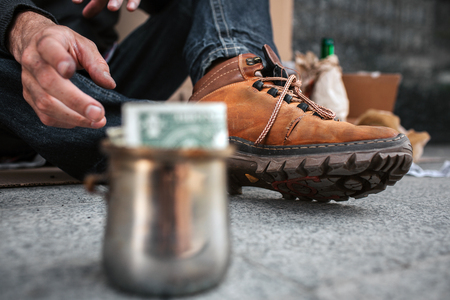 A picture that is focused on boots and a dirty hand of homeless man. He is reaching a cup that stands in front of him. There is a dollar in this metal cup. Stock Photo